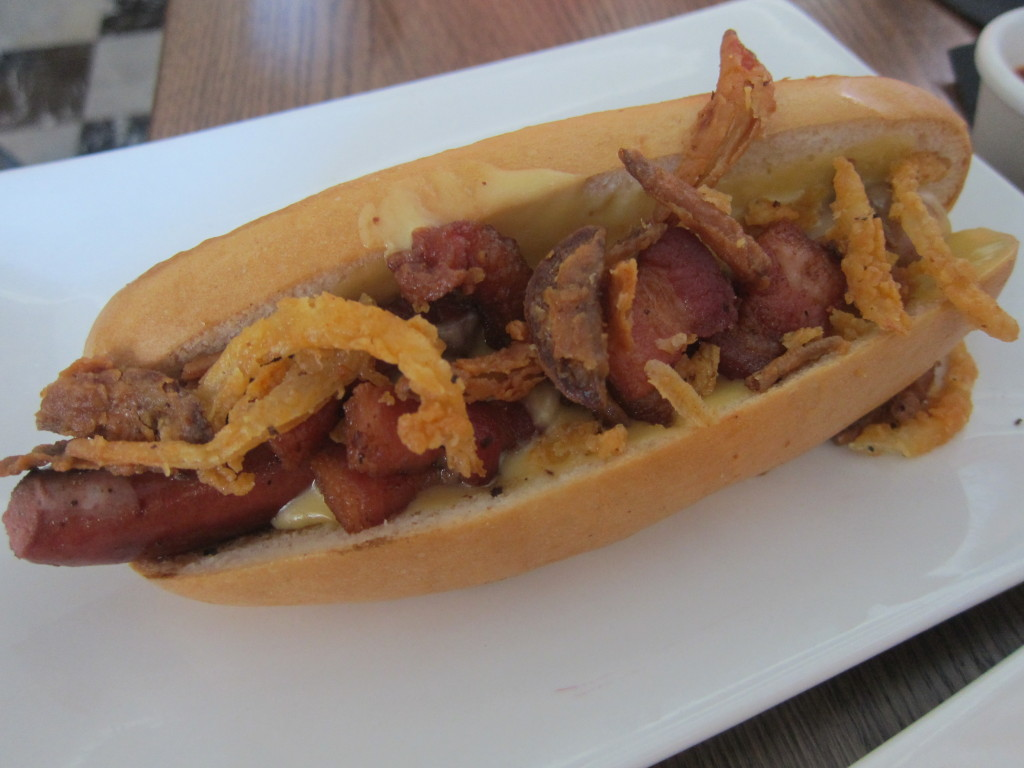 The Manly Dog with beer-cheddar cheese, minced bacon, onion strings, house ketchup and mustard spread