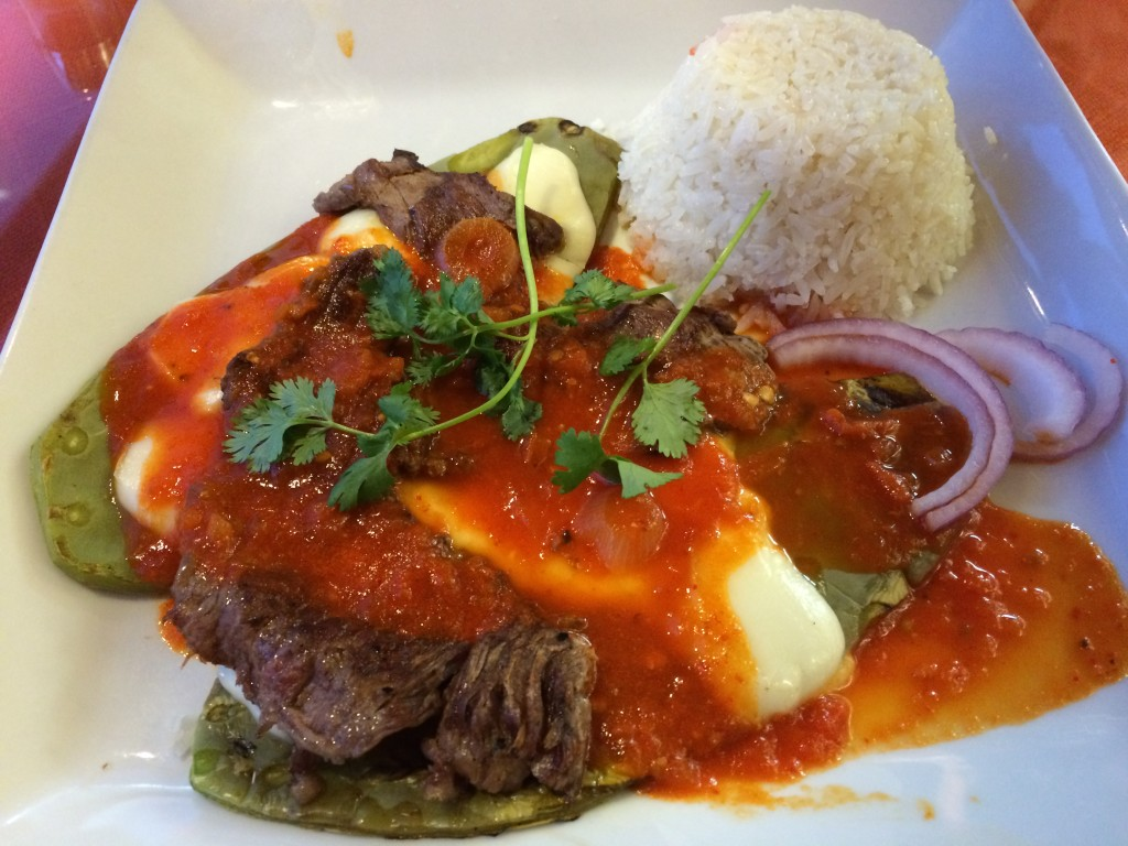 Conquista Plate with thin steak over grilled cactus, Oaxaca cheese and chile guajillo sauce